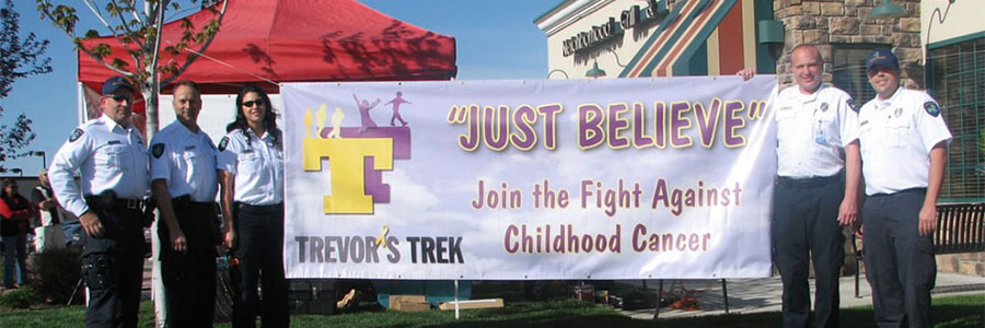 Trevors-Trek-Join-the-fight-against-childhood-cancer-foundation-banner-being held by Ada County Paramedics